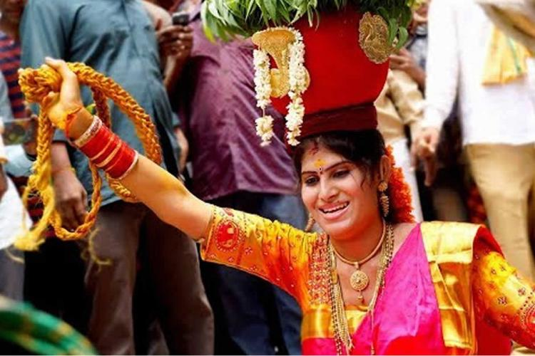 Trans woman Nishakranthi wearing a pink silk saree with golden border and gold jewellery with a decorated earthern Bonam pot balanced on her head performing at a Bonalu procession A crowd can be seen behind her watching the performance The Bonalu festival has become an empowering space for trans women in Telangana
