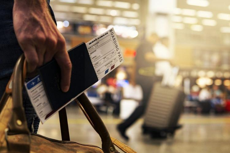 A person holding a bag along with passport and boarding pass in the right hand, airport in background,
