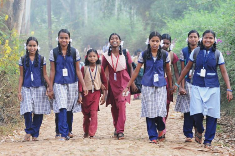 Children in school uniform from tribal areas are joining their hands and walking together as they go to school