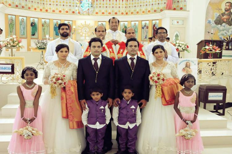 Twin priests conduct wedding of twin grooms with twin brides with twin pageboys and flower girls