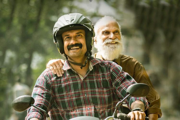 Actor Satyadev riding his bike wearing a helmet with an elderly man sitting behind