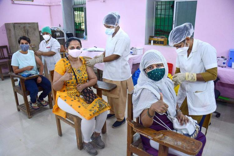 Three people get vaccinated against COVID-19 at a vaccination centre