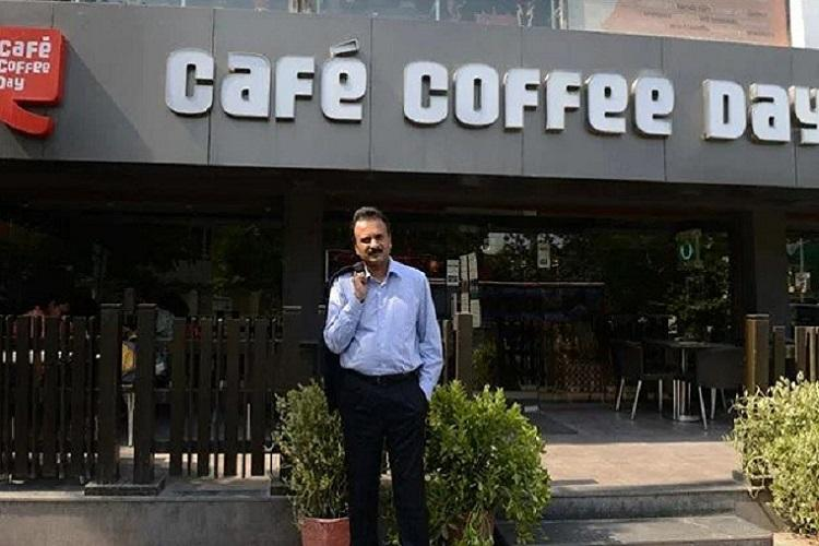 VG Siddhartha who is standing in the image in front of a Cafe coffee day store was the founder of Coffee Day and died by suicide last year due to mounting financial pressures