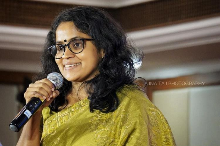 Filmmaker and former journalist Vidhu Vincent with a microphone at an event