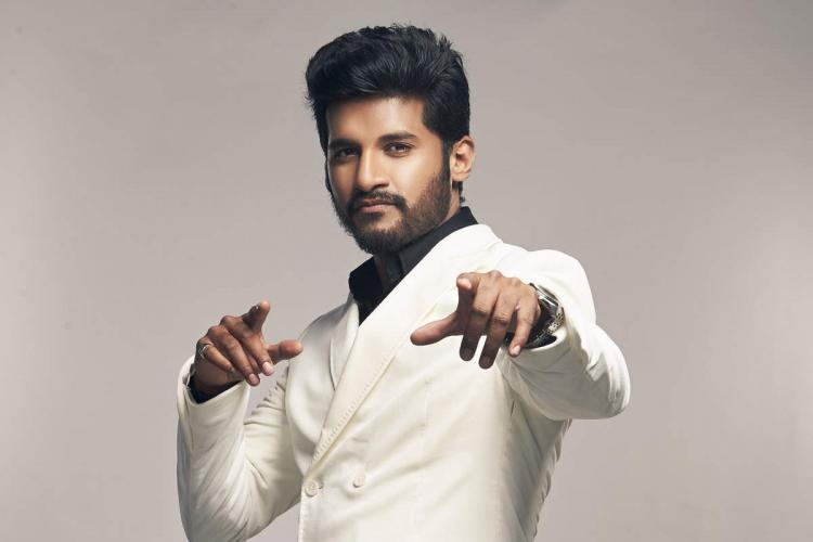 Vijay Yesudas in white suit with his hands pointed at the camera stands in style