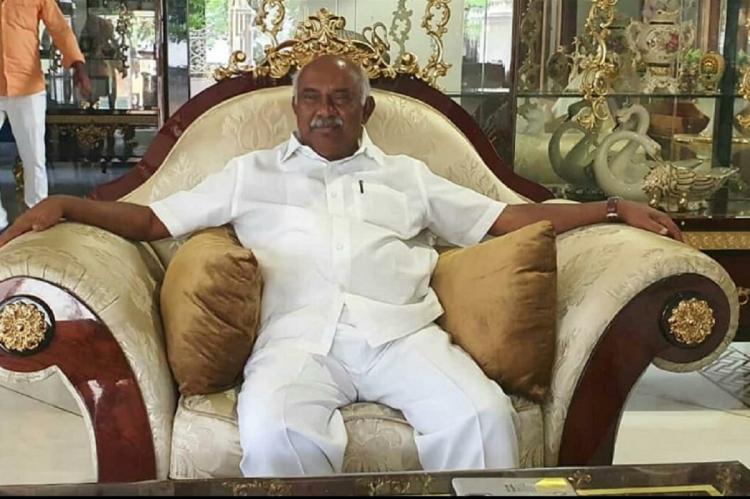 AH Vishwanath sitting on a white love seat with his arms rested on the chairs wing-backed arm rests