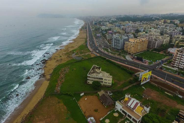 Aerial view of RK beach in Vizag with buildings on the right side of the beach road