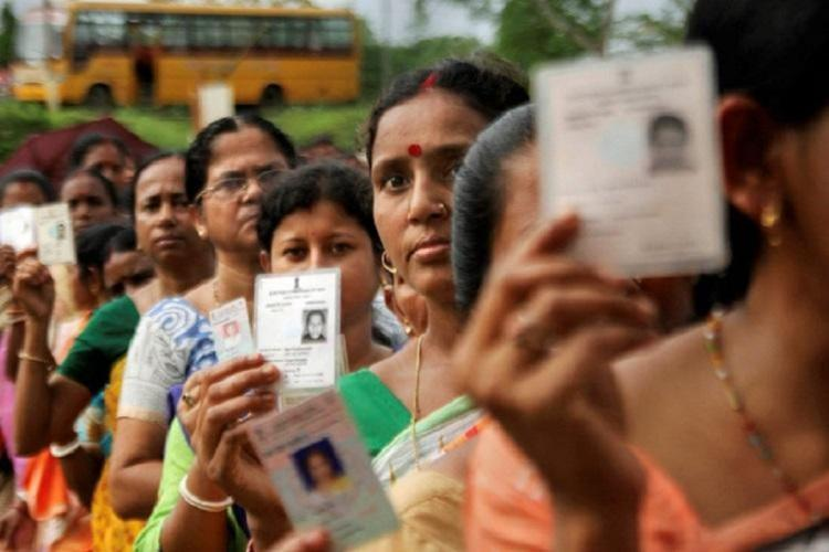 Women standing in queue and showing their voter ID