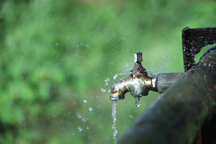 Photo of a running water tap near a field