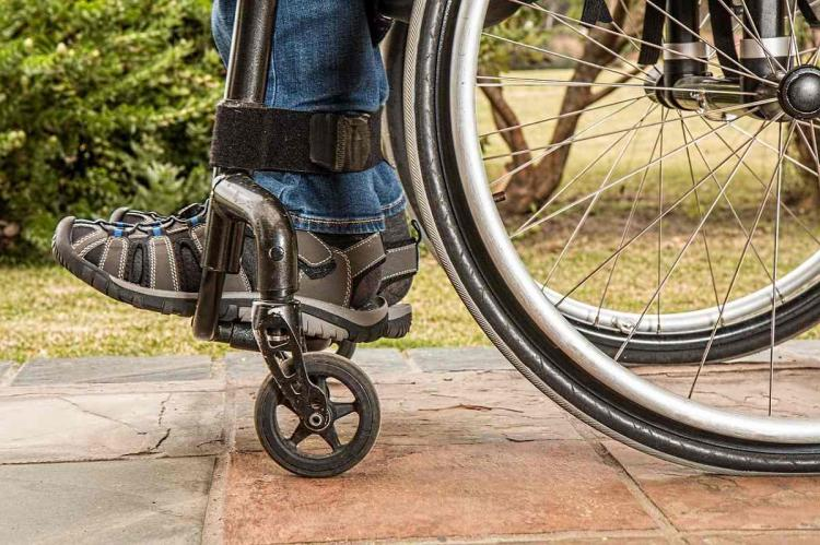 Close up of a person in a wheelchair his feet and sandals are visible
