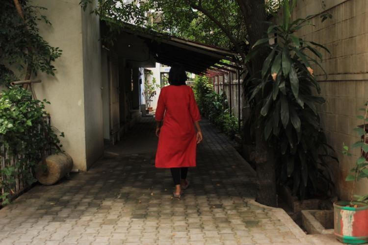 A woman wearing a red kurta walking back to the camera