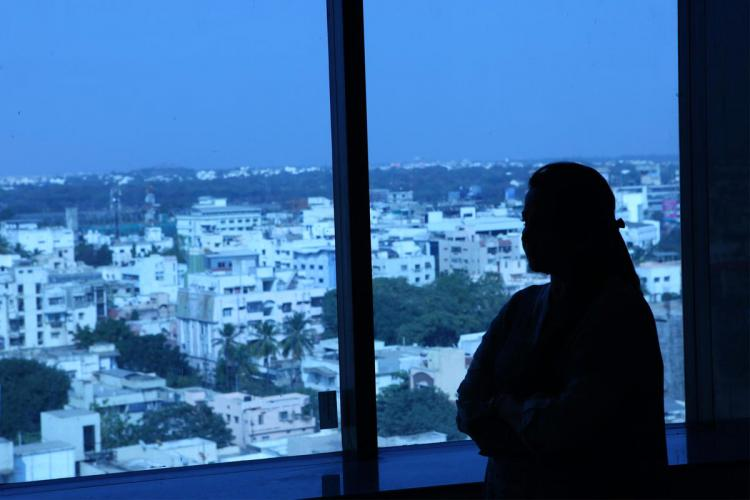 A woman stands by a window overlooking houses in a city
