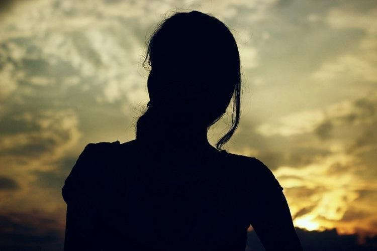 A woman in the dark facing the sky