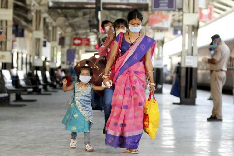 Woman walks with a girl child at airport wearing masks