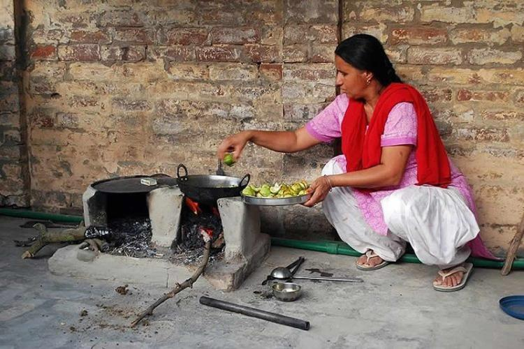 A woman in a pink kurta and red dupatta squatting beside a wood fire stove and cooking