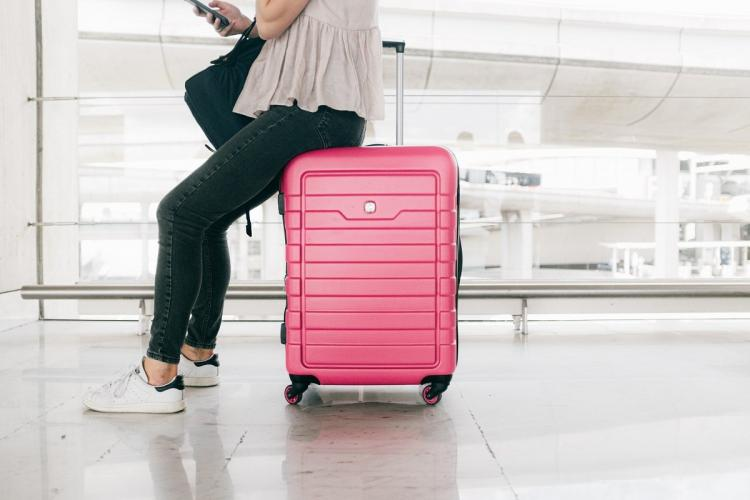 Woman wearing beige top black pants and sneakers sitting on a pink suitcase