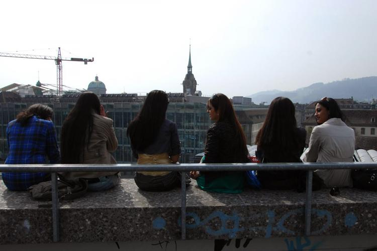 Young women sitting on a ledge with the view of the skyline talking to each other