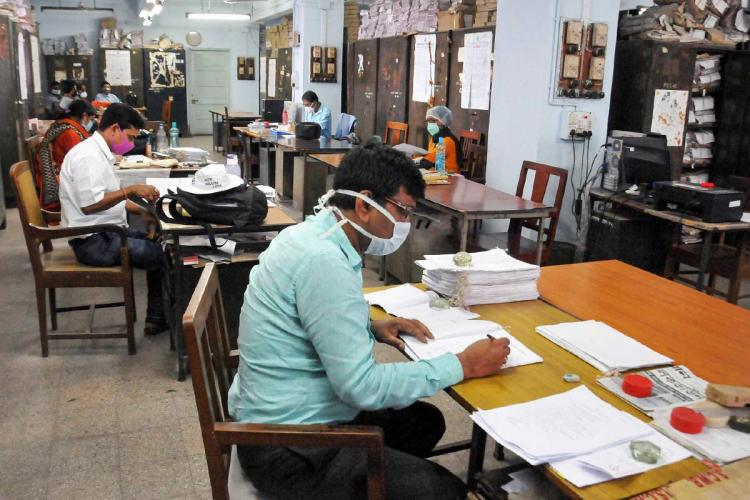 People work wearing masks at a co-working space