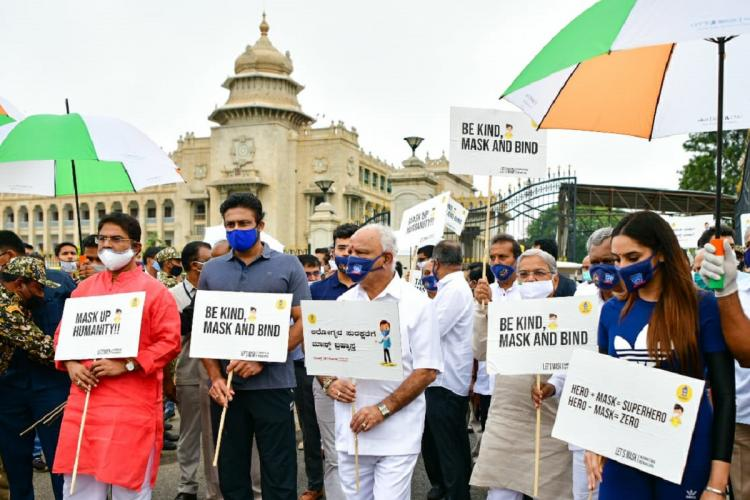 CM Yediyurappa holds a placard for mask day in front of the Vidhana Soudha in Bengaluru