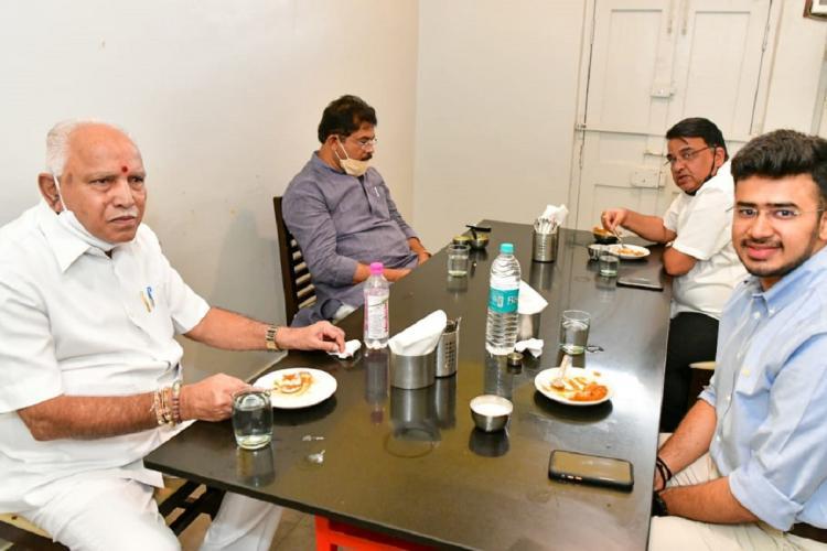 karnataka chief minister yediyurappa eats at a hotel in front of his sits tejasvi surya smiling