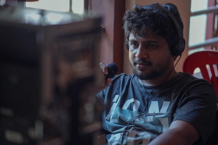 Zakariya wearing a dark blue t shirt is at work, wearing headphones and looking at a computer that's facing him