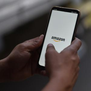 A man holding up a phone with Amazon app open