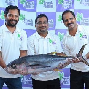 The founders of Fresh To Home standing in front of company branding, holding a huge fish