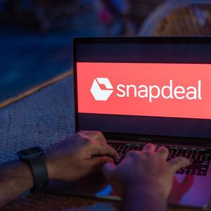 A person typing on a laptop, Snapdeal logo on screen