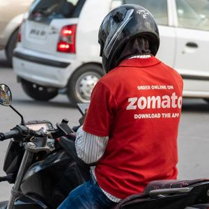 A Zomato rider sitting on a bike wearing the tshirt and helmet, photo taken from the back