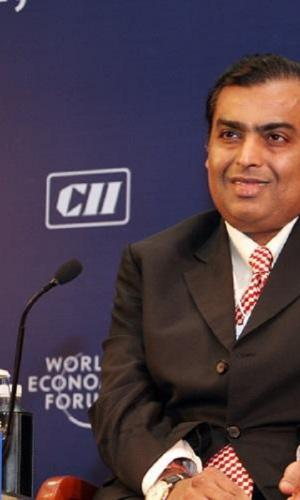 A file photo of Reliance Industries Chairman Mukesh Ambani who is seated at an event, slightly smiling with a mic in front of him