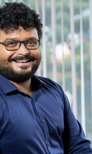 Anurag Bhatia portrait, wearing a blue shirt, open blinds in the background blurred