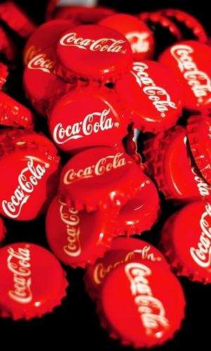A stack of Coca-Cola crown caps which are red in colour with the logo on them in white
