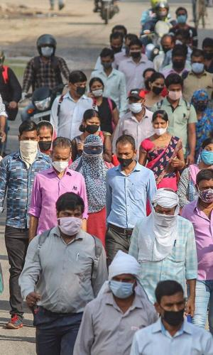 a large group of people walking, many wearing masks, picture taken at daytime