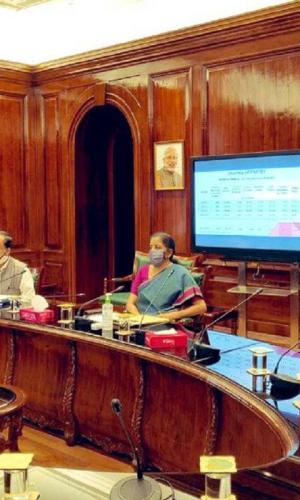 Nirmala Sitharaman in a grey saree sits with another Finance Minsitry official at her office where she is also seen wearing a mask as she interacts with other officials to review various schemes