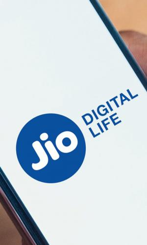 Jio Digital Life logo on a smartphone being held by a person, only hand and phone visible in frame