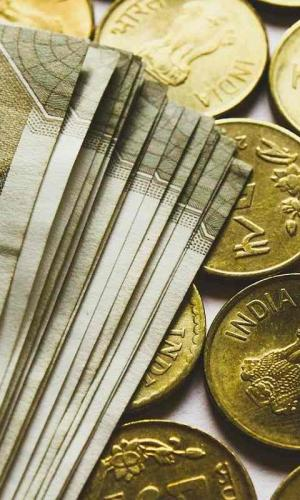 A stack of Rs 500 notes laid on Rs 5 coins
