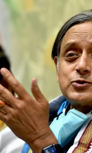 Shashi Tharoor speaking at a press conference with this mask down, photo taken from side left