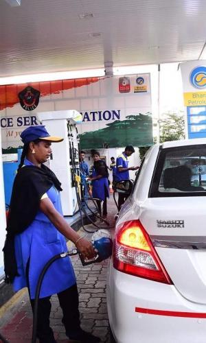A Bharat Petroleum woman employee filling fuel in a cab at a petrol bunk