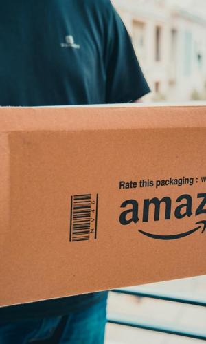 A delivery personnel holding a box with the Amazon logo on it