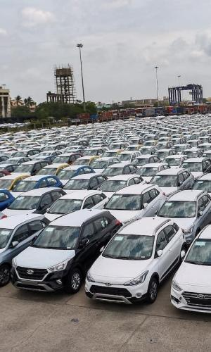 Hundreds of cars parked in a huge lot.