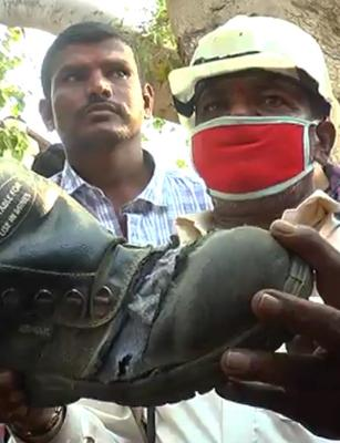 Hutti Gold Mine workers protest by holding up torn boots during Minister's visit