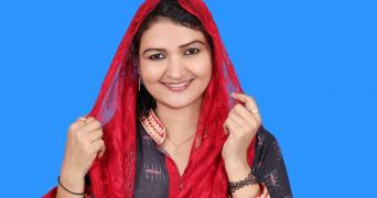 BJP candidate TP Sulfath in a navy blue kurta and a red dupatta draped over her head. She is smiling at the camera.