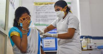 A health care worker vaccinating a lady on her hand who was wearing a saree