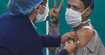 A female health professional administers the first dose of COVID-19 vaccine to a man who is seen showing the victory sign hand gesture.