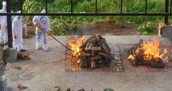 Two funeral pyres lit by health officials wearing ppe
