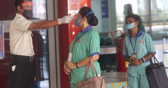 Security guard tests a nurse for fever with a handheld device another nurse waits in line