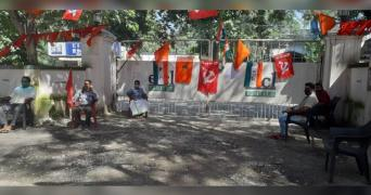 A few men sit maintaining distance in protest outside the gate of EICL, and many party flags can be seen hanging around them