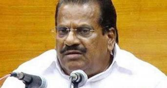 Jayarajan wearing a white shirt sits before two microphones against a mustard background
