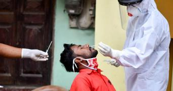 Technician in PPE takes nasal swab of an individual in Guwahati, Assam