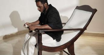 Man seated on a wired easy chair, reading a book